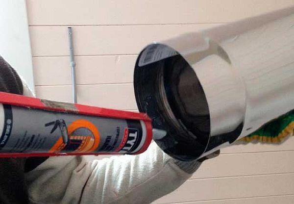Фото: склеивание дымохода из нержавейки при помощи герметизирующего клея
